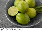 Купить «close up of limes in bowl on slate table top», фото № 29524514, снято 4 апреля 2018 г. (c) Syda Productions / Фотобанк Лори