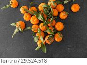 Купить «close up of mandarins on slate table top», фото № 29524518, снято 4 апреля 2018 г. (c) Syda Productions / Фотобанк Лори