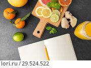 Купить «close up of fruits and notebook on slate table top», фото № 29524522, снято 4 апреля 2018 г. (c) Syda Productions / Фотобанк Лори