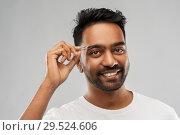 Купить «indian man with tweezers tweezing eyebrow hair», фото № 29524606, снято 27 октября 2018 г. (c) Syda Productions / Фотобанк Лори