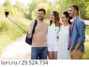 Купить «friends take picture by smartphone on selfie stick», фото № 29524734, снято 7 июля 2018 г. (c) Syda Productions / Фотобанк Лори