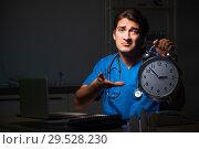 Купить «Young handsome doctor working night shift in hospital», фото № 29528230, снято 25 июля 2018 г. (c) Elnur / Фотобанк Лори