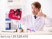 Купить «Young doctor with first aid kit in hospital», фото № 29528410, снято 23 августа 2018 г. (c) Elnur / Фотобанк Лори