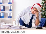 Купить «Young handsome employee celebrating Christmas at workplace», фото № 29528790, снято 30 июля 2018 г. (c) Elnur / Фотобанк Лори