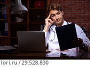 Купить «Young handsome doctor working night time at the hospital», фото № 29528830, снято 28 августа 2018 г. (c) Elnur / Фотобанк Лори