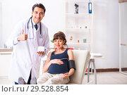 Купить «Young doctor checking pregnant woman's blood pressure», фото № 29528854, снято 30 июля 2018 г. (c) Elnur / Фотобанк Лори