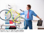 Купить «Young businessman using bike to commute to the office», фото № 29529050, снято 30 августа 2018 г. (c) Elnur / Фотобанк Лори