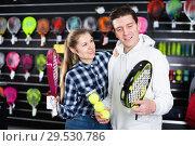 Купить «Sporty couple is demonstraiting modern racket and balls for padel», фото № 29530786, снято 7 февраля 2018 г. (c) Яков Филимонов / Фотобанк Лори