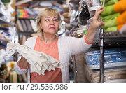 Customer woman choosing cotton tablecloths. Стоковое фото, фотограф Яков Филимонов / Фотобанк Лори