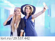 Купить «Two pretty young women taking selfie on the phone», фото № 29537442, снято 20 июля 2018 г. (c) Serg Zastavkin / Фотобанк Лори