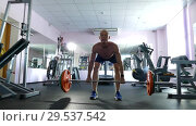 Купить «A young athletic man with a naked torso is engaged in physical work in the gym», видеоролик № 29537542, снято 12 января 2019 г. (c) Иван Карпов / Фотобанк Лори