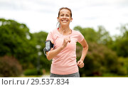 woman with earphones add armband jogging at park. Стоковое фото, фотограф Syda Productions / Фотобанк Лори