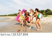 Купить «friends run with beach ball and swimming mattress», фото № 29537894, снято 29 июля 2018 г. (c) Syda Productions / Фотобанк Лори