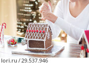 Купить «woman making gingerbread house on christmas», фото № 29537946, снято 30 октября 2014 г. (c) Syda Productions / Фотобанк Лори