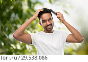 Купить «indian man brushing hair over natural background», фото № 29538086, снято 27 октября 2018 г. (c) Syda Productions / Фотобанк Лори