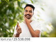 Купить «indian man applying natural grooming oil to beard», фото № 29538098, снято 27 октября 2018 г. (c) Syda Productions / Фотобанк Лори