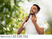 Купить «smiling indian man shaving beard with trimmer», фото № 29538102, снято 27 октября 2018 г. (c) Syda Productions / Фотобанк Лори