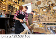 carpenters working with saw and wood at workshop. Стоковое фото, фотограф Syda Productions / Фотобанк Лори