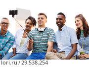 Купить «friends taking picture by on selfie stick in city», фото № 29538254, снято 10 июня 2018 г. (c) Syda Productions / Фотобанк Лори