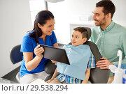 Купить «dentist showing tablet pc to kid at dental clinic», фото № 29538294, снято 22 апреля 2018 г. (c) Syda Productions / Фотобанк Лори