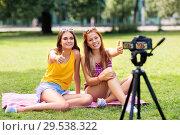 Купить «teenage bloggers recording video by camera in park», фото № 29538322, снято 19 июля 2018 г. (c) Syda Productions / Фотобанк Лори