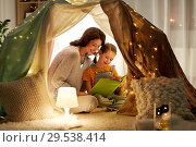 Купить «happy family reading book in kids tent at home», фото № 29538414, снято 27 января 2018 г. (c) Syda Productions / Фотобанк Лори