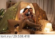 Купить «happy couple with smartphone in kids tent at home», фото № 29538418, снято 27 января 2018 г. (c) Syda Productions / Фотобанк Лори
