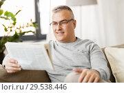 Купить «man reading newspaper at home», фото № 29538446, снято 14 апреля 2018 г. (c) Syda Productions / Фотобанк Лори