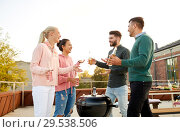 Купить «happy friends having bbq party on rooftop», фото № 29538506, снято 2 сентября 2018 г. (c) Syda Productions / Фотобанк Лори