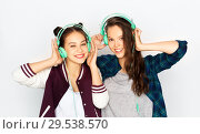 Купить «teenage girls in earphones listening to music», фото № 29538570, снято 19 декабря 2015 г. (c) Syda Productions / Фотобанк Лори