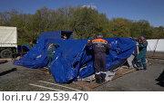 Купить «Group of rescuers setting up an army field tent, deploy campground on windy day», видеоролик № 29539470, снято 2 октября 2018 г. (c) А. А. Пирагис / Фотобанк Лори
