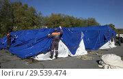 Купить «Group of rescuers setting up an army field tent, deploy campground on windy day», видеоролик № 29539474, снято 2 октября 2018 г. (c) А. А. Пирагис / Фотобанк Лори