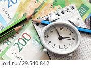 Купить «Российские деньги, часы-будильник, блокнот для записей и карандаши. Бизнес-натюрморт», фото № 29540842, снято 7 декабря 2018 г. (c) Наталья Осипова / Фотобанк Лори