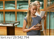 Купить «Girl holding guidebook in museum of art, mother on background», фото № 29542794, снято 21 октября 2018 г. (c) Яков Филимонов / Фотобанк Лори