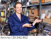 Купить «Young woman worker in uniform showing construction materials at shelves», фото № 29542802, снято 20 сентября 2018 г. (c) Яков Филимонов / Фотобанк Лори