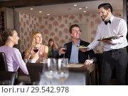 Купить «Waiter bringing delicious salads to visitors of restaurant», фото № 29542978, снято 8 января 2018 г. (c) Яков Филимонов / Фотобанк Лори