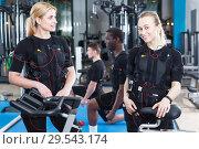 Купить «girls dressed EMS vests before training», фото № 29543174, снято 16 апреля 2018 г. (c) Яков Филимонов / Фотобанк Лори