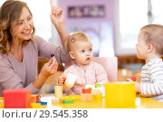 Educator and children having fun on learning in kindergarten. Teacher, education, kids and primary school concept . Стоковое фото, фотограф Оксана Кузьмина / Фотобанк Лори