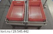 Купить «Red plastic boxes are moved along a roller conveyor», видеоролик № 29545442, снято 28 октября 2018 г. (c) Андрей Радченко / Фотобанк Лори
