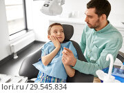 Купить «father supporting son at dental clinic», фото № 29545834, снято 22 апреля 2018 г. (c) Syda Productions / Фотобанк Лори