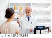 Купить «apothecary with cure and customer at pharmacy», фото № 29545918, снято 27 июня 2015 г. (c) Syda Productions / Фотобанк Лори