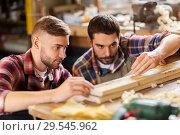 carpenters measuring wooden board at workshop. Стоковое фото, фотограф Syda Productions / Фотобанк Лори
