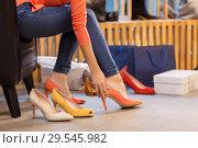 Купить «young woman trying high heeled shoes at store», фото № 29545982, снято 22 сентября 2017 г. (c) Syda Productions / Фотобанк Лори
