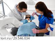 Купить «dentist treating kid teeth at dental clinic», фото № 29546034, снято 22 апреля 2018 г. (c) Syda Productions / Фотобанк Лори
