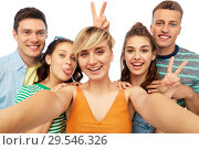 Купить «happy friends taking selfie and showing peace», фото № 29546326, снято 30 июня 2018 г. (c) Syda Productions / Фотобанк Лори
