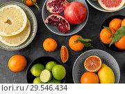 Купить «close up of citrus in bowls fruits on stone table», фото № 29546434, снято 4 апреля 2018 г. (c) Syda Productions / Фотобанк Лори