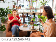 Купить «female friends drinking tea and talking at cafe», фото № 29546442, снято 7 августа 2018 г. (c) Syda Productions / Фотобанк Лори