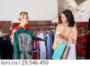 Купить «women choosing clothes at vintage clothing store», фото № 29546450, снято 7 августа 2018 г. (c) Syda Productions / Фотобанк Лори