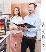 Купить «Couple choosing kitchen furniture materials», фото № 29546754, снято 11 апреля 2018 г. (c) Яков Филимонов / Фотобанк Лори