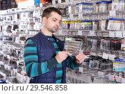 Купить «Young male customer choosing new fishing lures», фото № 29546858, снято 16 января 2018 г. (c) Яков Филимонов / Фотобанк Лори